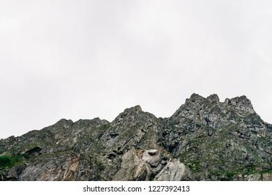 Giant ridge under cloudy sky. Misty rocky mountainside with vegetation. Amazing mountain range in overcast weather. Unusual foggy rocks. Atmospheric landscape of majestic nature of highlands.