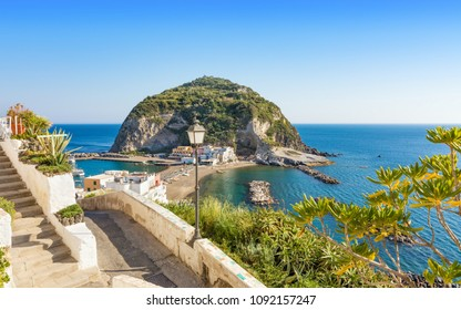 Giant rock with green trees on top near small village Sant'Angelo on Ischia island, region Campania in Italy