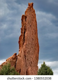 A giant rock pinnacle jutting straight up from the ground and green vegetation at Garden of the Gods Park in Colorado.