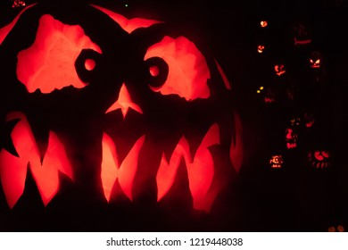 Giant scary Halloween pumpkin in the foreground of some holiday decorations