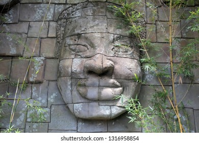 Giant smiling Buddha face on a temple wall in South East Asia.