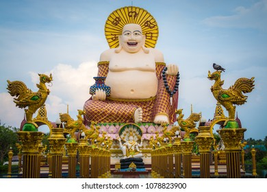 Giant smiling or happy buddha statue with blue sky in buddhist temple ( wat plai laem ), Koh Samui, Thailand.