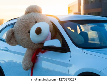 Giant teddy bears with red ribbons sitting on top of the car hood outdoor. Space for text. Love, valentines day concept