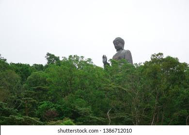 The giant Tian Tan Buddha statue up on high green mountain near Po Lin Monastery in Ngong Ping village, Lantau Island, Hong Kong