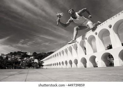 Giant torchbearer athlete hurdling with sport torch in monochrome over the Arcos da Lapa Arches in Rio de Janeiro, Brazil