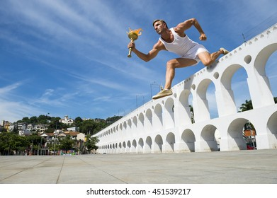 Giant torchbearer athlete hurdling with sport torch over the Arcos da Lapa Arches in Rio de Janeiro, Brazil