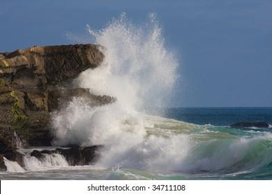 Giant wave crashing against rocky coastline