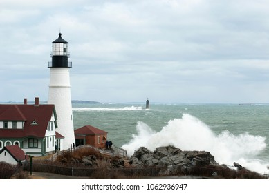 Giant waves caused by rare high tides break between Portland Head light and Ram Island Ledge lighthouse in Maine.