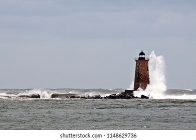 Giant waves crash around the stone lighthouse tower of Whaleback light in Maine.