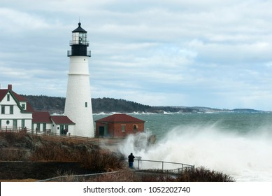 Giant waves crash by Portland Head lighthouse from rare high tides in late winter in Maine.