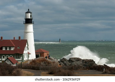 Giant waves crash over rocks by Portland Head lighthouse and out at Ram Island Ledge light as sun breaks through sotrm clouds in Maine.