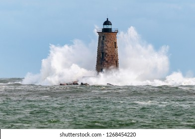 Giant waves from a distinctive high tide surround stone tower of Whaleback lighthouse in Maine.
