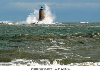 Giant waves surround stone lighthouse tower of Whalback light in Maine during a unique high tide.