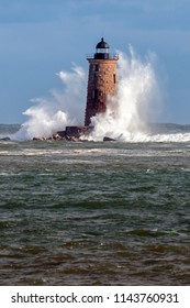 Giant waves surround the stone tower of Whaleback lighthouse from a rare high tide on a sunny day in Maine.