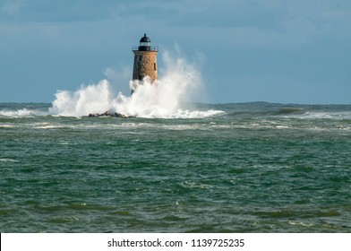 Giant waves from a unique high tide surround stone lighthouse tower of Whaleback light as sun breaks through clouds in southern Maine.