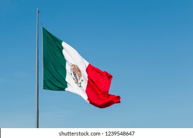 Giant waving flag of Mexico with a blue sky.