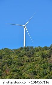 Giant wind turbine on a hill against blue sky