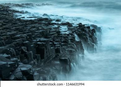 Giant's Causeway basalt rocks pattern. Long exposure, ocean waves with basalt rocks in Northern Ireland.