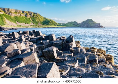 Giants Causeway, unique geological hexagonal formation of volcanic basalt rocks and cliffs in Antrim County, Northern Ireland, in sunset light