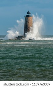 Giat waves from a unique high tide surround the stone tower of Whaleback lighthouse as the sun illuminates the structure in Maine.