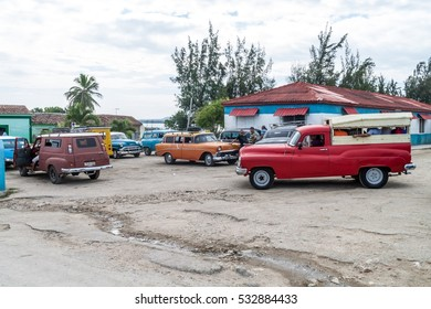 GIBARA,  CUBA - JAN 29, 2016: Old cars serving as shared taxis wait at the transport terminal in Gibara village