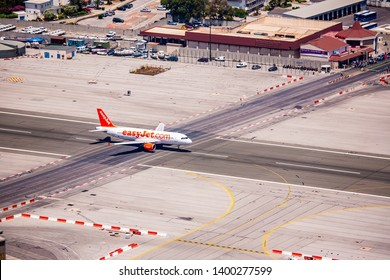Gibraltar 02 July 2011: Easyjet plane as it is taking off on the runway at Gibraltar airport, at the same time some people wait to cross the runway as soon as the plane has taken off