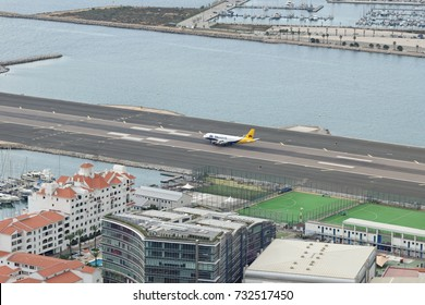 GIBRALTAR - AUGUST 29, 2017: The bay of Gibraltar with the airport runway strip with a landed Monarch airplane on it.