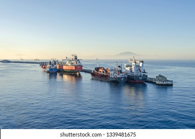 Gibraltar, British Overseas Territory -  November 8, 2018: Harbor and the Bay of Gibraltar with commercial vessels OBO-Carrier SKS Tanaro, chemical Tankers C Rock and Fionia Swan at sunrise