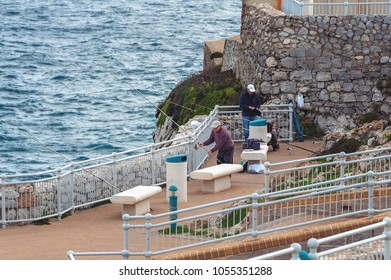 GIBRALTAR, EUROPE - DECEMBER 2017: Fishermen are catching fish at southern part of the city, located at Europa point.