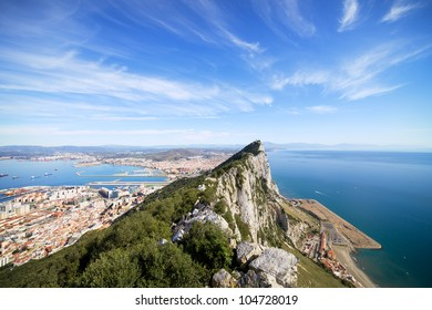 Gibraltar Rock view from above, on the left Gibraltar town and bay, La Linea town in Spain at the far end, Mediterranean Sea on the right.
