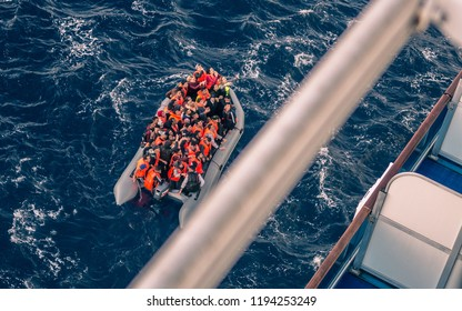 Gibraltar Straight/Spain - 10/02/2018: Muslim refugees trying to evacuate, in Spain, Europe on small motorboat, begging for help from a big cruise ship in the sea.