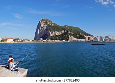 GIBRALTAR, UK - APRIL 20, 2009 - The rock seen across the bay from Spain with a family fishing in the foreground, Gibraltar, United Kingdom, Western Europe, April 20, 2009.