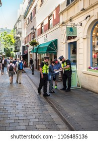 Gibraltar, UK - May 18, 2017: Police Officers gives direction advice to tourists at Main Street of Gibraltar, United Kingdom, Western Europe.