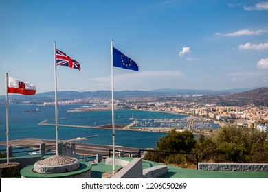 Gibraltar, United Kingdom, 1st October 2018:- View from the top of the Rock  into Spain, with the flags of Gibraltar, UK and EU flying. Gibraltar is a British Overseas Territory.