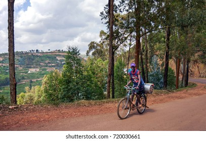 GICUMBI, RWANDA - JUNE 3, 2016: a man on a bicycle transporting a large can is working hard to climb the RN3 Byumba - Kigali road along the Muvumba river valley. .