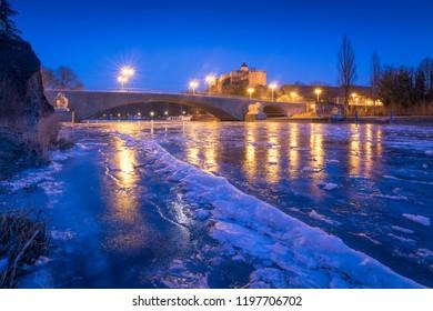 Giebichenstein Castle in Halle and frozen river Saale at dusk in winter