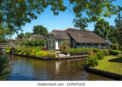GIETHOORN - JULY 2: View of famous village of Giethoorn in The Netherlands on 2 July 2018. Giethoorn is the most famous village in The Netherlands and receives around 800.000 tourists per year.