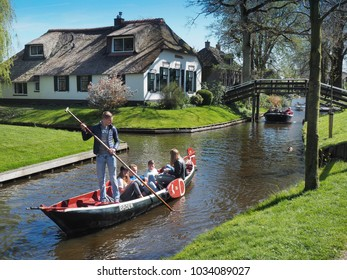 GIETHOORN, THE NETHERLANDS - APRIL 21: Tourists enjoy punting a boat around Giethoorn village in the Netherlands on April 21, 2016