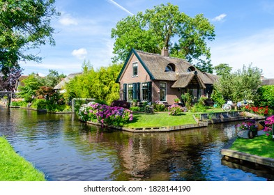 """GIETHOORN, NETHERLANDS - JULY 17,2016: Landscape view of famous Giethoorn village with canals and rustic thatched roof houses. The beautiful houses and gardening city is know as """"Venice of the North""""."""