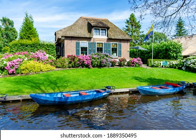"""GIETHOORN, NETHERLANDS - JULY 17,2016: Landscape view of famous Giethoorn village with canals and rustic thatched roof houses. The beautiful houses and gardening city is know as """"Venice of the North"""""""