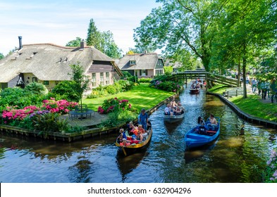 """GIETHOORN, NETHERLANDS - JULY 17,2016: view of typical houses of Giethoorn on July 17, 2016 in Giethoorn,The Netherlands. The beautiful houses and gardening city is know as """"Venice of the North""""."""