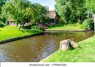 """Giethoorn, Netherlands: Landscape view of famous Giethoorn village with canals and rustic thatched roof houses. The beautiful houses and gardening city is know as """"Venice of the North""""."""