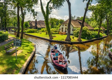 Giethoorn, Netherlands - May 30, 2018 : Tourists on a sightseeing boat in the dutch village of Giethoorn. Giethoorn is often referred to as Little Venice, or the Venice of the North.
