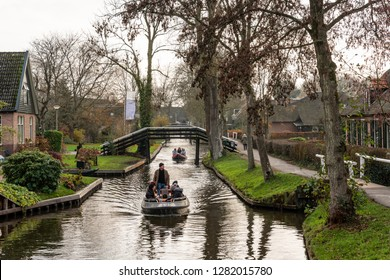 GIETHOORN, NETHERLANDS - NOVEMBER 24, 2018: Green winter scene of people in two small boats cruising on narrow canals among buildings in the famous village Giethoorn Netherlands November 24, 2018.