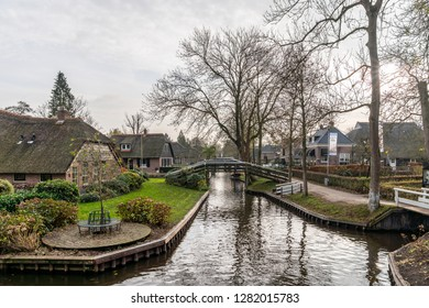 GIETHOORN, NETHERLANDS - NOVEMBER 24,  2018: Green winter scene of narrow canals among residential buildings in the famous village Giethoorn Netherlands November 24, 2018.