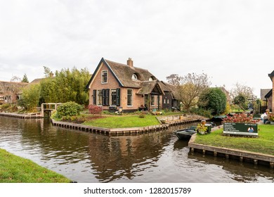 GIETHOORN, NETHERLANDS - NOVEMBER 24,  2018: Beautiful green winter scene of narrow canals and residential buildings with boats and signs in the famous village Giethoorn Netherlands November 24, 2018.