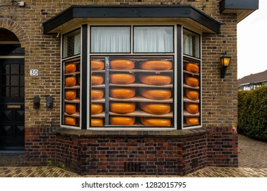 GIETHOORN, NETHERLANDS - NOVEMBER 24,  2018: Closeup facade front view of a cheese store window with round yellow cheese stickers, brown brick building in Giethoorn Netherlands November 24, 2018.