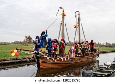 GIETHOORN, NETHERLANDS - NOVEMBER 24, 2018: Traditional celebration of Sinterklaas, Black Peter. People with makeup and colorful costumes on a wooden boat on a canal in Giethoorn November 24,2018.