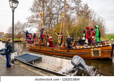 GIETHOORN, NETHERLANDS - NOVEMBER 24, 2018: Traditional festival celebration of Sinterklaas. People with makeup and colorful costumes on a wooden boat on a canal in Giethoorn November 24, 2018.