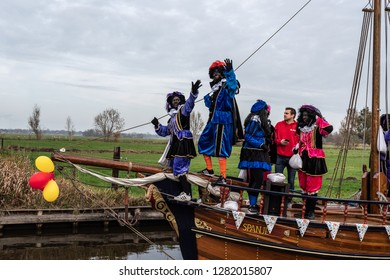 GIETHOORN, NETHERLANDS - NOVEMBER 24, 2018: Traditional  celebration of Sinterklaas, Black Peter. People with makeup and colorful costumes on a wooden boat on a canal in Giethoorn November 24, 2018.